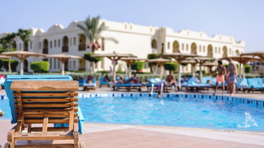 International pool/spa/patio expo 2020 las vegas | wooden recliner chair standing on paving overlooking resort swimming pool | international pool/spa/patio expo 2020