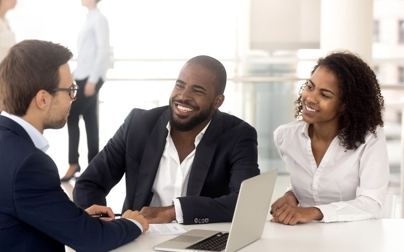 Excited african american couple talk male realtor   berkshire hathaway homeservices sales convention 2021