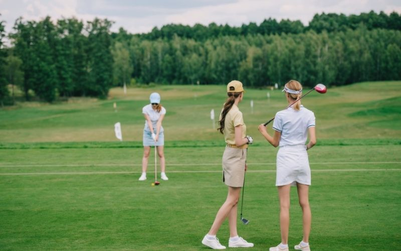 Selective focus of women in caps with golf equipment looking at friend playing golf   golf fest las vegas 2020