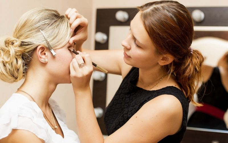Woman applying makeup for a bride on her wedding day | cosmoprof north america 2021